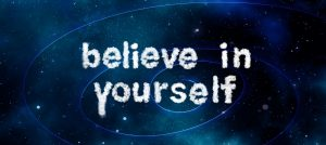 the words believe in yourself written in chalky style font on stars and planets background