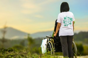 person in wheelchair with support worker looking at a scenic view with mountains in the background
