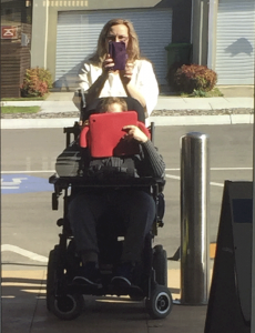 photo of person in wheelchair taking picture with iPad and carer taking picture with iPhone